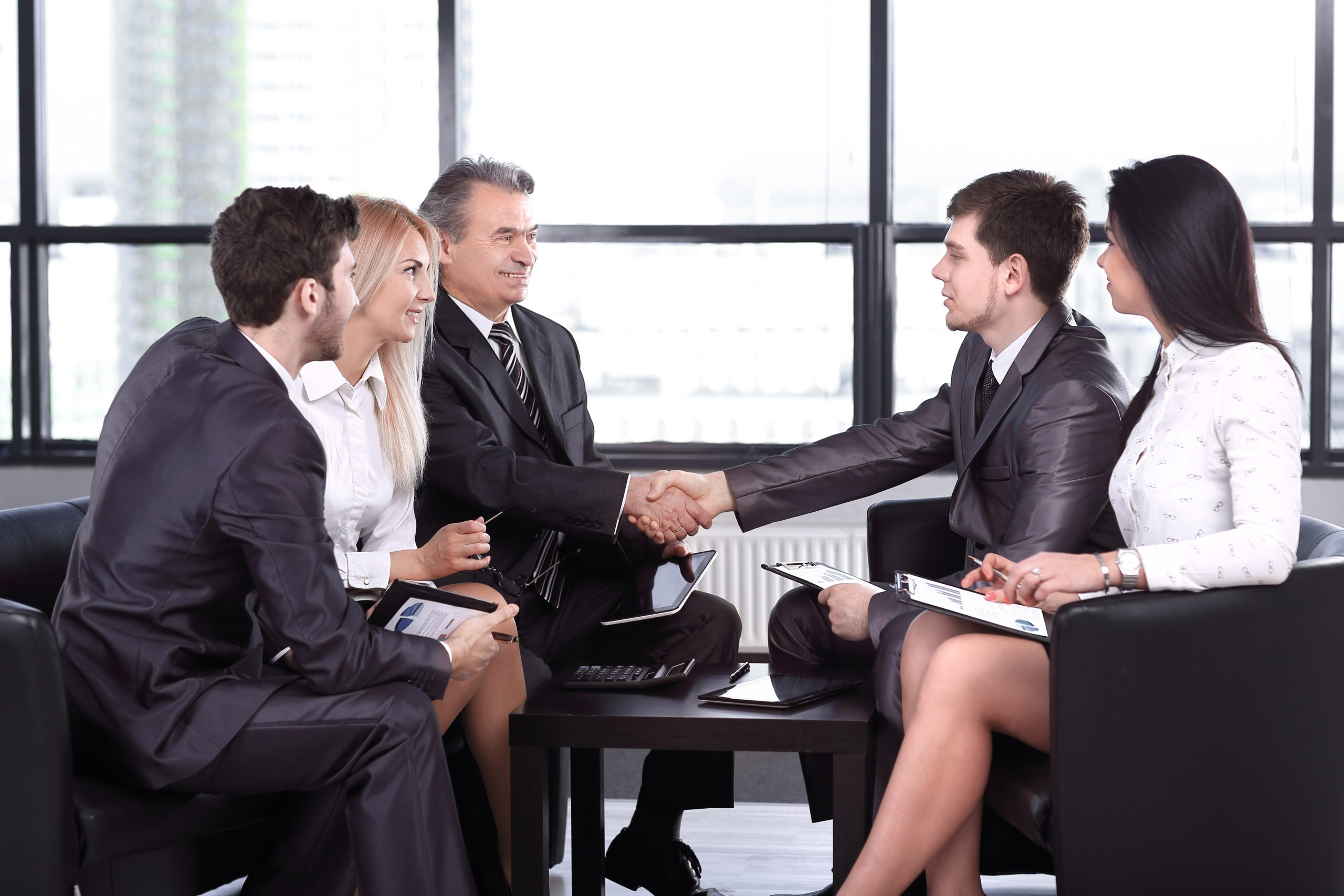 employees look at the handshake of business partners scaled